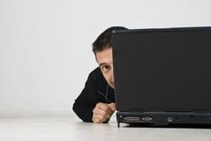 Hombre que mira y que oculta detrás de la computadora portátil Imagen de archivo
