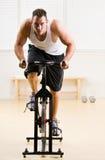 Hombre que monta la bicicleta inmóvil en club de salud Fotos de archivo libres de regalías