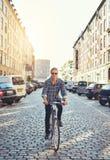 Hombre que monta su bici a través de la ciudad Foto de archivo