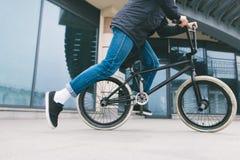 Hombre que monta una bici de BMX en la ciudad en el fondo de la arquitectura cycling Cultura de BMX fotos de archivo