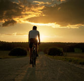 Hombre que monta una bicicleta en la puesta del sol Imágenes de archivo libres de regalías