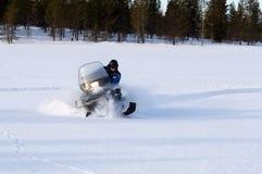 Hombre que monta una moto de nieve Imágenes de archivo libres de regalías