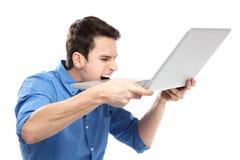 Hombre que muerde una computadora portátil en la frustración Foto de archivo libre de regalías