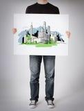Hombre que muestra al tablero blanco con bosquejo de la ciudad Imagenes de archivo