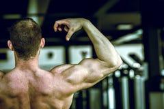 Hombre que muestra detrás en gimnasio Fotografía de archivo