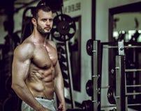 Hombre que muestra el ABS en gimnasio Imagenes de archivo