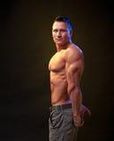 Hombre que muestra el músculo del tríceps Imágenes de archivo libres de regalías
