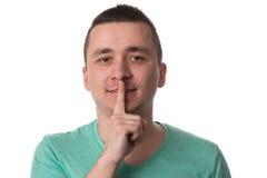 Hombre que muestra gesto de Shh en el fondo blanco Fotos de archivo libres de regalías