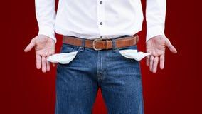 Hombre que muestra su bolsillo vacío en fondo rojo de la pared imágenes de archivo libres de regalías
