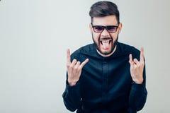 Hombre que muestra su lengua sobre fondo gris fotos de archivo libres de regalías