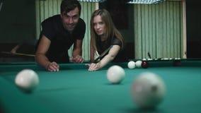 Hombre que muestra a su muchacha donde golpear la bola - mujer joven que recibe consejo sobre bola de piscina del tiroteo mientra metrajes