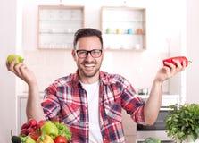 Hombre que muestra verduras en cocina Foto de archivo libre de regalías