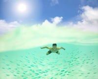 hombre que nada bajo la superficie del mar con los pescados fotografía de archivo libre de regalías