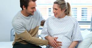 Hombre que obra recíprocamente con la mujer embarazada en sala almacen de video