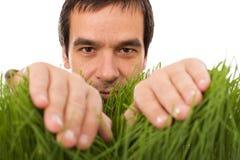 Hombre que oculta detrás de las láminas de la hierba Fotos de archivo libres de regalías