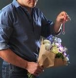 Hombre que oculta el anillo de compromiso en un ramo Imágenes de archivo libres de regalías