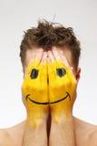 Hombre que oculta su cara bajo máscara de la sonrisa Fotografía de archivo
