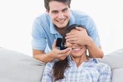 Hombre que oculta sus ojos de las novias y que le ofrece un compromiso r Foto de archivo