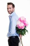 Hombre que oculta una flor detrás el suyo detrás. Imágenes de archivo libres de regalías