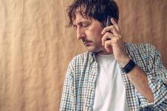 Hombre que oye malas noticias en el teléfono Imagen de archivo libre de regalías