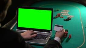 Hombre que paga apuesta del póker con la tarjeta de crédito, usando la pantalla del verde del ordenador portátil, en línea ganand metrajes