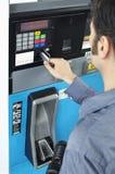 Hombre que paga con la tarjeta de crédito en el surtidor de gasolina Imágenes de archivo libres de regalías
