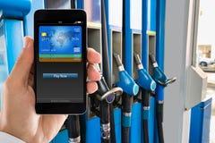 Hombre que paga con Smartphone en la gasolinera fotos de archivo libres de regalías