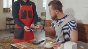 Hombre que paga el desayuno en el café almacen de video