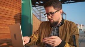 Hombre que paga en línea usando el ordenador portátil almacen de metraje de vídeo