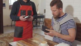 Hombre que paga la comida en café almacen de metraje de vídeo