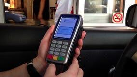 Hombre que paga la tarjeta de crédito dentro del coche