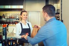 Hombre que paga orden para llevar por la tarjeta de crédito en el lector holded por la camarera sonriente que trabaja en el resta fotos de archivo libres de regalías