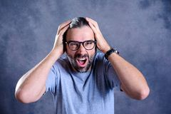 Hombre que parece chocado y que lleva a cabo su cabeza Foto de archivo libre de regalías