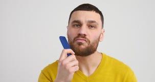 Hombre que peina su barba almacen de metraje de vídeo