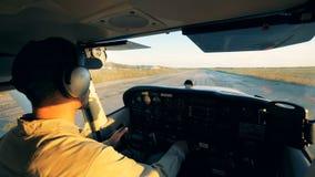Hombre que pilota un aeroplano en un campo de aviación, visión trasera metrajes