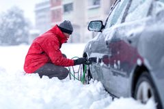 Hombre que pone cadenas de nieve en el neumático de coche fotografía de archivo libre de regalías
