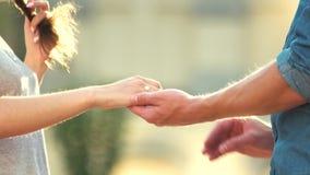 Hombre que pone el anillo de compromiso en la mano de la mujer al aire libre metrajes