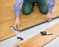Hombre que pone el color laminado de los paneles de la madera imagenes de archivo