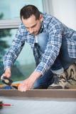 Hombre que pone el suelo laminado en concepto de la construcción fotos de archivo