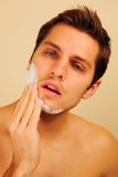 Hombre que pone en la crema de afeitar Fotografía de archivo
