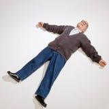 Hombre que pone en la tierra con los brazos outstretched Imagenes de archivo