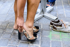 Hombre que pone en los zapatos de los tacones altos foto de archivo