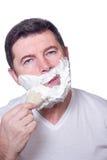 Hombre que pone espuma de la barba imagenes de archivo