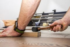 Hombre que pone la lamina usando el martillo y el bloque de madera imagen de archivo
