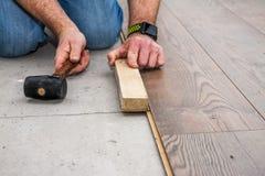 Hombre que pone la lamina usando el martillo y el bloque de madera imágenes de archivo libres de regalías