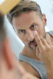 Hombre que pone las lentes de contacto en sus ojos foto de archivo