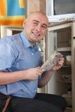 Hombre que pone pescados en el refrigerador Fotos de archivo