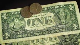 Hombre que pone seis monedas en dos billetes de dólar en superficie oscura almacen de metraje de vídeo