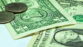 Hombre que pone seis monedas en el billete de dólar dos
