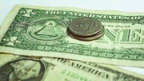 Hombre que pone una torre de monedas en dos billetes de dólar